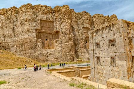 guia de turismo: Naqsh-e Rostam, IRÁN - 03 de mayo 2015: El grupo de turistas con el guía la salida a la construcción del cubo en forma de Cubo de Zoroastro, siglo quinto antes de Cristo torre aqueménida de la era de la antigua necrópolis cerca ruinas de la antigua ciudad de Persépolis. Editorial