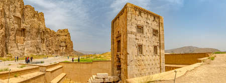 bce: NAQSH-E RUSTAM, IRAN - MAY 3, 2015: The group of tourists with the tour guide checking out the Cube shaped construction Cube of Zoroaster, 5th century B.C.E. Achaemenid-era tower of ancient necropolis near ruins of old city Persepolis. Editorial