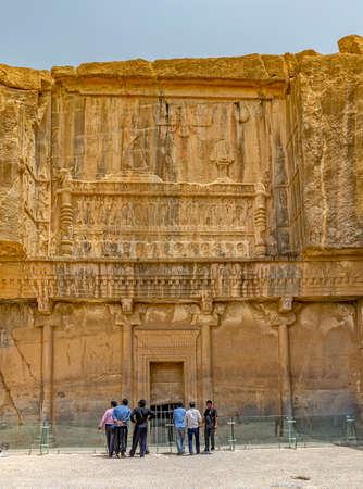 fars: PERSEPOLIS, IRAN - MAY 3, 2015: tourists sightseeing royal tombs ruins of old city, a capital of the Achaemenid Empire 550 - 330 BC.