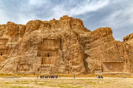 guia turistico: Naqsh-e Rostam, IRÁN - 03 de mayo 2015: El grupo de turistas con el guía delante de los monumentos históricos de la antigua necrópolis cerca de las ruinas de la antigua ciudad de Persépolis.