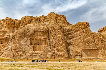 tour guide: NAQSH-E RUSTAM, IRAN - MAY 3, 2015: The group of tourists with the tour guide in front of the historical monuments of ancient necropolis near ruins of old city Persepolis. Editorial