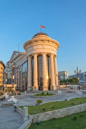 macedonian: SKOPJE, MACEDONIA - JULY 17, 2015: Macedonian archaeological museum famous building in sunset and the pedestrians passing by. Editorial