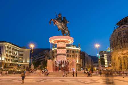 alexander the great: SKOPJE, MACEDONIA - JULY 17, 2015: Long exposure night scene of the people walking by the fountain with statue of Alexander the Great on top in the middle of the main square in downtown of capital city.
