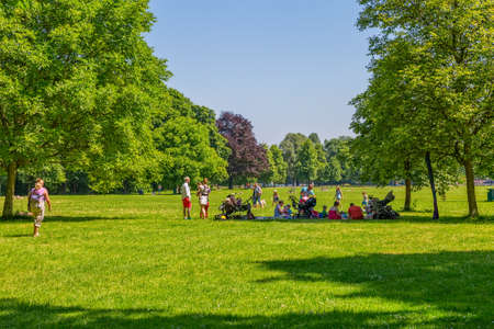 english famous: MUNICH, GERMANY - JUNE 4, 2015: People enjoying the sunny day with family and friends in English garden, famous city park.