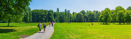garden city: MUNICH, GERMANY - JUNE 4, 2015: Panoramic view of the people enjoying the sunny day by walking in English garden, famous city park.