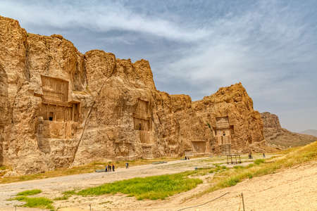 necropolis: NAQSH-E RUSTAM, IRAN - MAY 3, 2015: Tourists sightseeing the historical monuments of ancient necropolis near ruins of old city Persepolis.