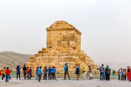 cyrus: PASARGAD, IRAN - MAY 4, 2015: The group of tourists with the tour guide checking out the tomb of Cyrus the Great. Editorial