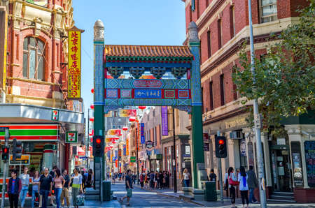 MELBOURNE, AUSTRALIA - MARCH 21, 2015: People walking by the Chinatown entrance arches on Little Bourke Street. Редакционное