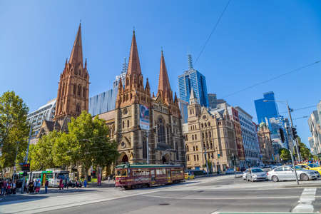 informative: MELBOURNE, AUSTRALIA - MARCH 21, 2015: The historic and informative City Circle Tram popular with tourists travels passes by the St. Paul Cathedral and Flinders Street Station crossroad. Editorial