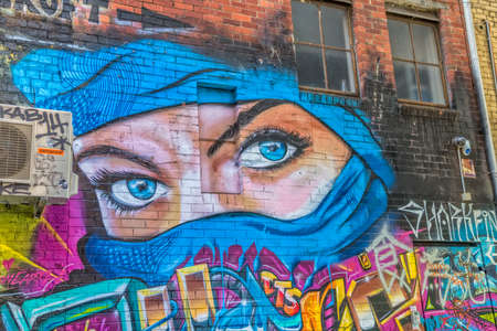 croft: MELBOURNE, AUSTRALIA - MARCH 21, 2015: Colorful graffiti in Croft Alley in downtown, depicts an blue eyes of a woman in a blue scarf.