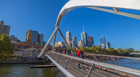 southbank: MELBOURNE, AUSTRALIA - MARCH 21, 2015: People crossing the Southbank footbridge on the Yarra River on the beautiful sunny day.