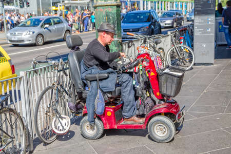 special needs: MELBOURNE, AUSTRALIA - MARCH 21, 2015: A man sitting in a vehicle for people with special needs and sells small religious booklet in front of Flinders Street Station.