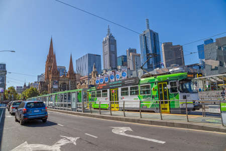 flinders: MELBOURNE, AUSTRALIA - MARCH 21, 2015: Trams on Flinders Street tram stop near thr Federation Square and Cathedral of Saint Paul on the beautiful sunny day.