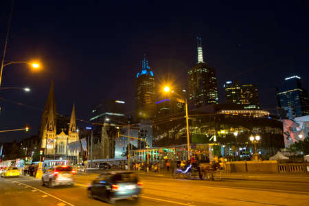 flinders: MELBOURNE, AUSTRALIA - MARCH 21, 2015: Traffic on Flinders Street near thr Federation Square and Cathedral of Saint Paul at night. Editorial