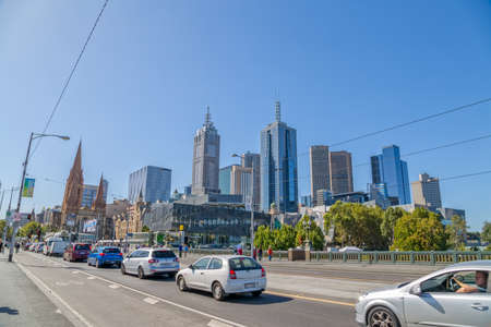 flinders: MELBOURNE, AUSTRALIA - MARCH 21, 2015: Traffic on Flinders Street near thr Federation Square and Cathedral of Saint Paul on the beautiful sunny day.