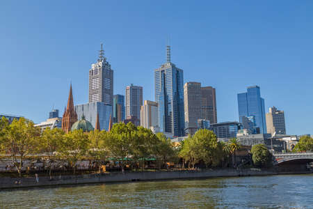 southbank: MELBOURNE, AUSTRALIA - MARCH 21, 2015: View of the city from Southbank showing Cathedral of Saint Paul and apartment architecture on the beautiful sunny day.