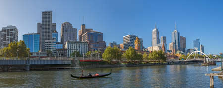 southbank: MELBOURNE, AUSTRALIA - MARCH 21, 2015: Panoramic view of the city from Southbank and a romantic ride in a gondola with the gondolier, on Yarra River at autumn season. Editorial