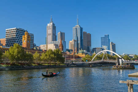 southbank: MELBOURNE, AUSTRALIA - MARCH 21, 2015: View of the city from Southbank and a romantic ride in a gondola with the gondolier, on Yarra River at autumn season.