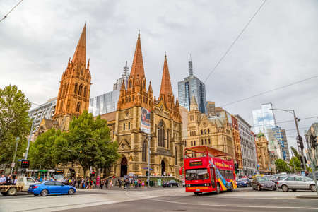 st: MELBOURNE, AUSTRALIA - MARCH 17, 2015: The informative City Soghtseeng bus popular with tourists travels passes by the St. Paul Cathedral and Flinders Street Station crossroad.