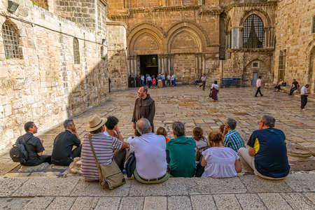 holiest: JERUSALEM, ISRAEL - JUNE 19, 2015: Monk and pilgrims at the atrium of the Church of the Holy Sepulchre, holiest Christian site in the world.