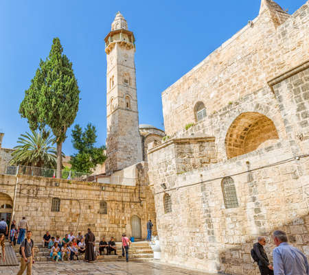 atrium: JERUSALEM, ISRAEL - JUNE 19, 2015: People resting at atrium of the Church of the Holy Sepulchre in front of the Omer mosque minaret.