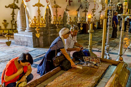 sepulchre: JERUSALEM, ISRAEL - JUNE 19, 2015: People make pilgrimages to the Stone of Anointing in Church of the Holy Sepulchre.