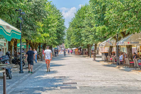 locals: CETINJE, MONTENEGRO - AUGUST 11, 2015: Tourists and locals passing by in a leisurely stroll on the Njegoseva street.