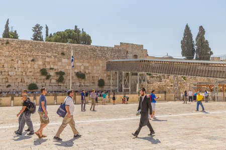 kotel: JERUSALEM, ISRAEL - JUNE 19, 2015: Tourists passing by the Western Wall, Wailing Wall or Kotel is located in the Old City of Jerusalem at the foot of the western side of the Temple Mount.