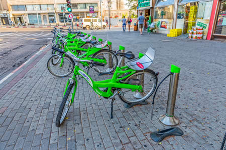 parked bikes: TEL AVIV, ISRAEL - JUNE 19, 2015: City Bikes for rent parked in the Ben Yehuda street near the Arcadia Tower hotel. Editorial