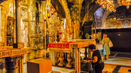 church of the holy sepulchre: JERUSALEM, ISRAEL - JUNE 19, 2015: Pilgrims praying at the altar erected over the place of the crucifixion of Jesus Christ in Church of the Holy Sepulchre. Editorial