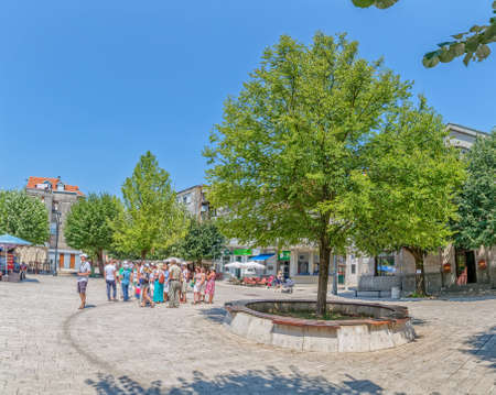 leisurely: CETINJE, MONTENEGRO - AUGUST 11, 2015: Tourists and locals passing by in a leisurely stroll on the Dvorski Square. Editorial