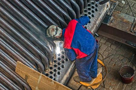 over the shoulder: Welder welding metal pipes. Over shoulder shot. Stock Photo
