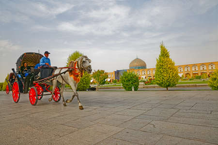 ISFAHAN, IRAN - MAY 7, 2015: Tourists enjoy riding a carriage on the Imam square.
