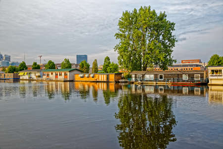Amsterdam floating houses in river Amstel channel Фото со стока