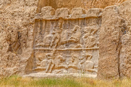 Ancient relief of the necropolis Naqsh-e Rustam that shows the equestrian victory of Bahram II over enemy, near ruins of Persepolis.