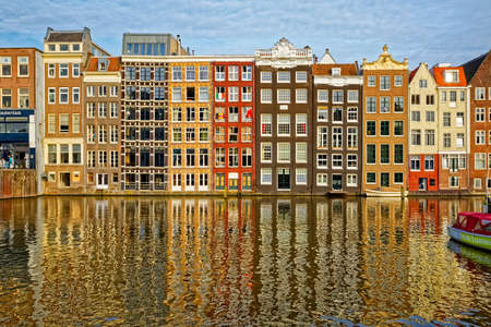 AMSTERDAM, NETHERLANDS - JUNE 12, 2016: Narrow old housing buildings with reflection in a water canal of the river Amstel.