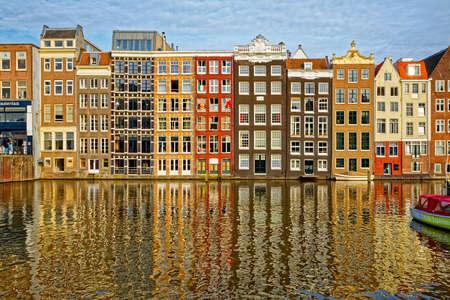 AMSTERDAM, NIEDERLANDE - 12. JUNI 2016: Schmale alte Wohngebäude mit Reflexion in einem Wasserkanal des Flusses Amstel.