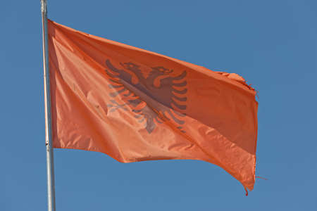 Fluttering Albanian flag on blue sky in background.