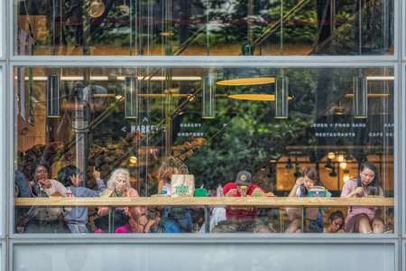 People eat at Whole Foods Market restaurant opposite the Bryant Park, New York