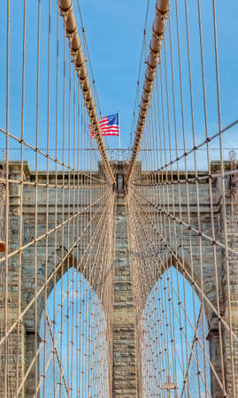 The United States flag on center of Brooklyn Bridge in New York, Vertically oriented shot Фото со стока