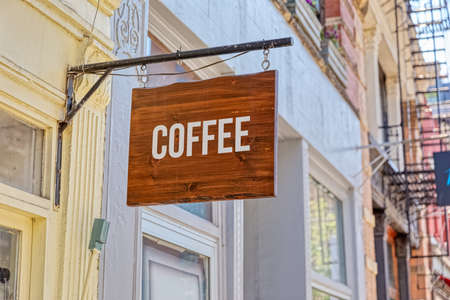 Wooden coffe sign on a facade