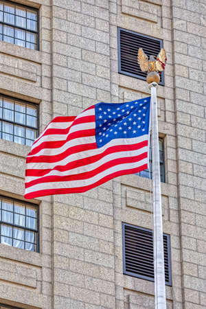 USA flag in New York, unfurled and fluttering, mounted on a city park yardarm.