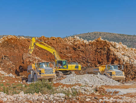 Excavator and trucks at a road construction site
