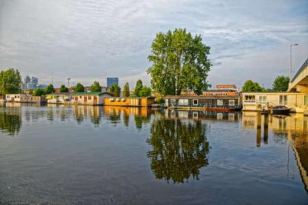 Amsterdam floating houses in river Amstel channel Zdjęcie Seryjne