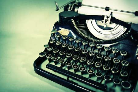 Vintage handmatige schrijfmachine gefotografeerd tegen een schemerige teal achtergrond.