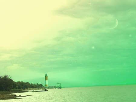 haz: Sea landscape with lighthouse and the birth of the green night of waning moon Paisagem do mar com farol eo nascimento da noite verde da lua minguante  Stock Photo