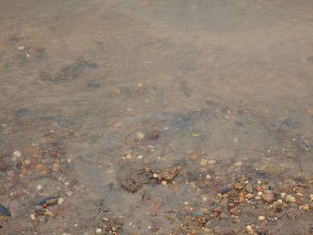 textura: acqua del fiume sulla sabbia e piccoli sassi sulla costa