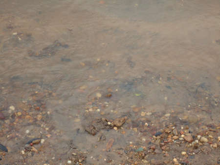 textura: river water on sand and small stones on the coast