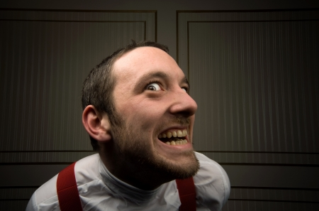 dirty teeth: young male looks crazed with stubble and dirty teeth