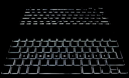backlit keyboard: COMMUNICATE is spelled out on a backlit keyboard with reflection